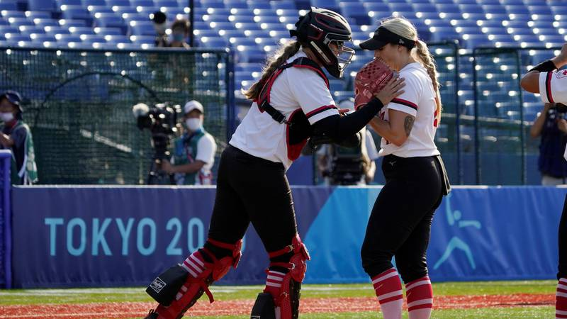 Canada's Kaleigh Rafter, left, talks with pitcher Danielle Lawrie, right, in the seventh inning...