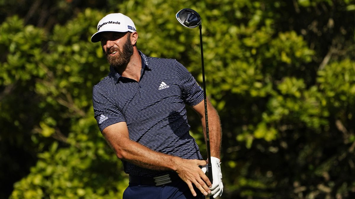 Dustin Johnson watches his drive on the fifth tee during the final round of the Masters golf...