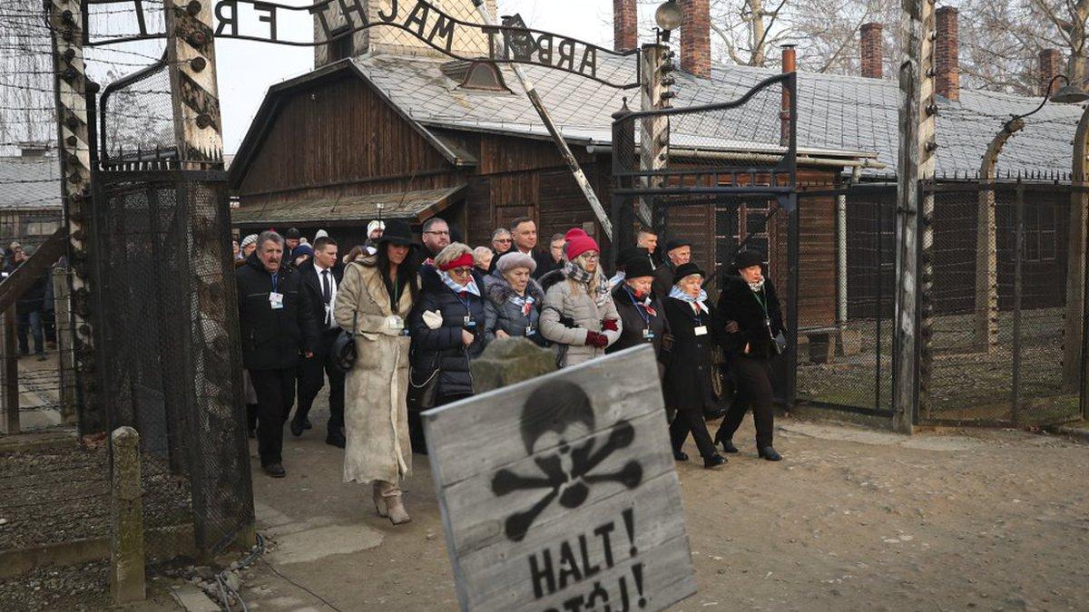 Poland's President Andrzej Duda walks along with survivors through the gates of the Auschwitz...