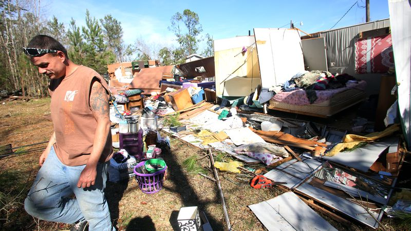 Ernest Creamer, 30, walks carefully through the debris from his tornado damaged mobile home in...