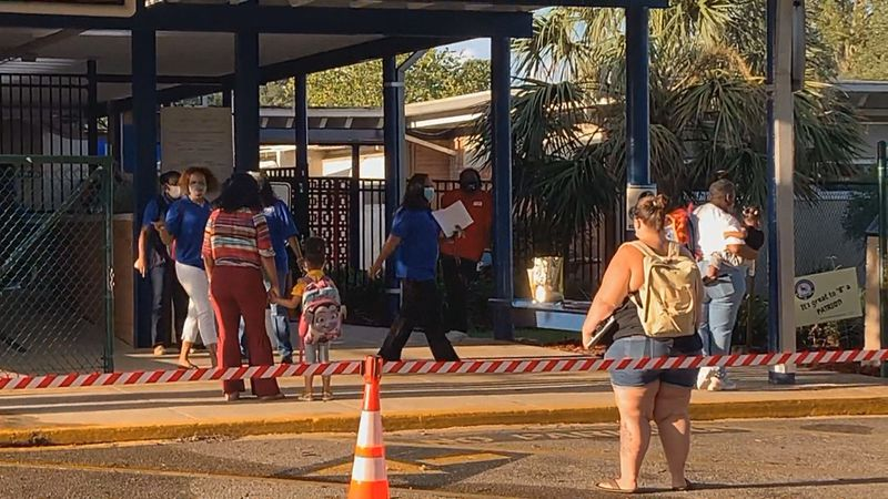 At Sabal Palm Elementary School, students lined up before the first bell to get temperature...