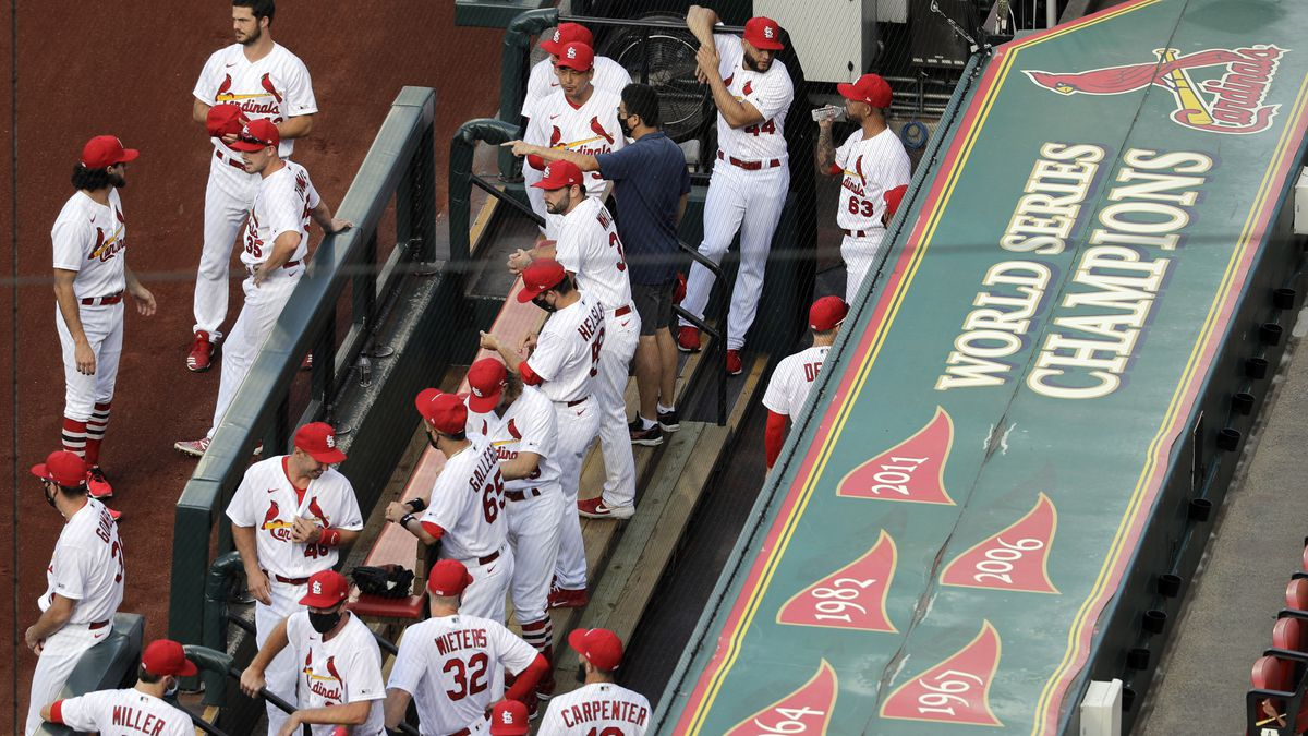 In this July 24, 2020, file photo, members of the St. Louis Cardinals wait to be introduced before the start of a baseball game against the Pittsburgh Pirates in St. Louis. The Cardinals 4-game series against the Detroit Tigers was postponed Monday, Aug. 3, 2020, after more Cardinals players and staff staffers test positive for COVD-19. The series was to have been played in Detroit from Tuesday through Thursday. (AP Photo/Jeff Roberson, File)