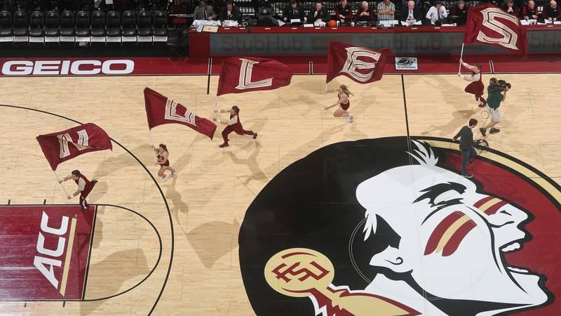 Florida State flag bearers run across the floor before the start of an NCAA college basketball...