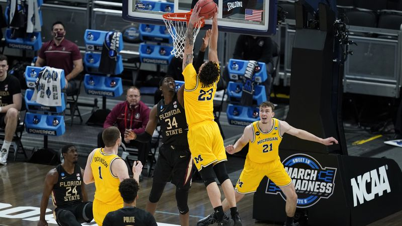 Michigan forward Brandon Johns Jr. (23) dunks over Florida State center Tanor Ngom (34) during...