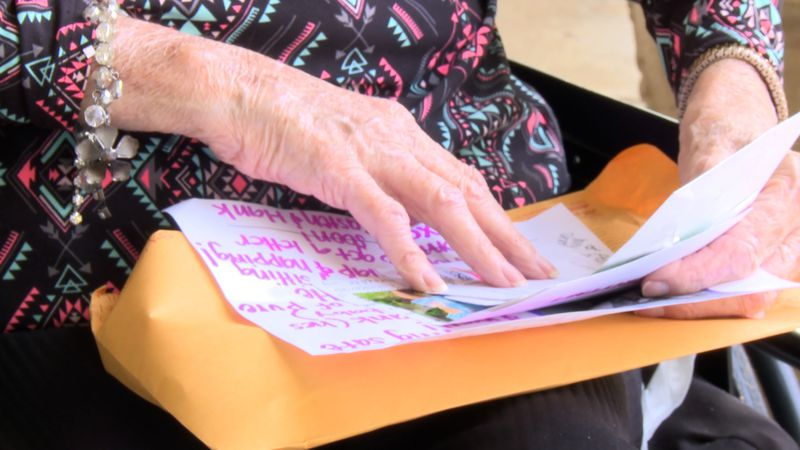 A resident at an assisted living facility reads letters from her pen pals.