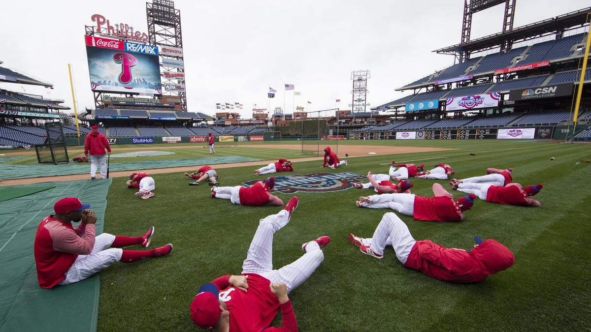 FILE - In this April 7, 2017, file photo, members of the Philadelphia Phillies stretch before the team's baseball game against the Washington Nationals in Philadelphia. Five players for the Philadelphia Phillies have tested positive for COVID-19 at the team's spring camp in Florida, prompting the club to indefinitely close the complex. The team also said Friday, June 19, 2020, that three staff members at the camp have tested positive. The club didn't identify any of those affected.