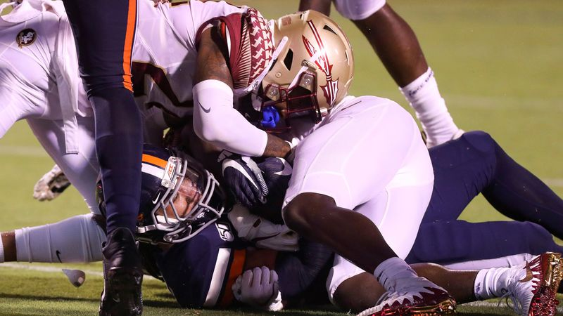 Virginia running back Wayne Taulapapa (21) scores a touchdown under Florida State defensive...