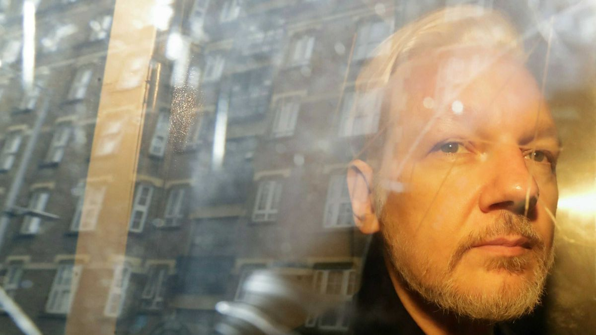 In this Wednesday, May 1, 2019 file photo, buildings are reflected in the window as WikiLeaks founder Julian Assange is taken from court, where he appeared on charges of jumping British bail seven years ago, in London. (AP Photo/Matt Dunham)