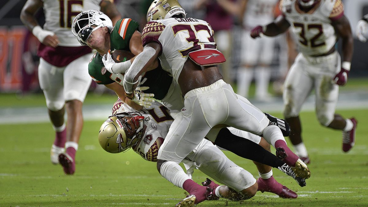 Miami tight end Will Mallory is sandwiched between Florida State defenders Jaiden Lars-Woodbey and Amari Gainer during the first half of their game, Saturday, September 26, 2020.
