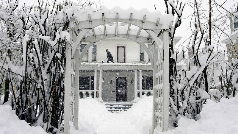 FILE - Amber Cox shovels snow from the porch roof at her home in Auburn, Maine, on March 8,...