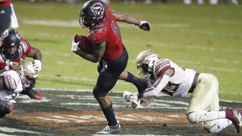 N.C. State running back Ricky Person Jr. (8) tries to escape from Florida State linebacker...
