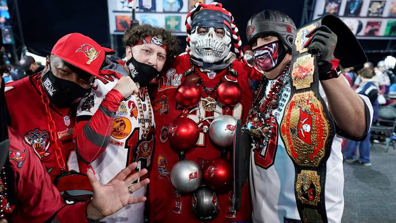 A group of Tampa Bay Buccaneer fans dressed to support their team await the the first round of...