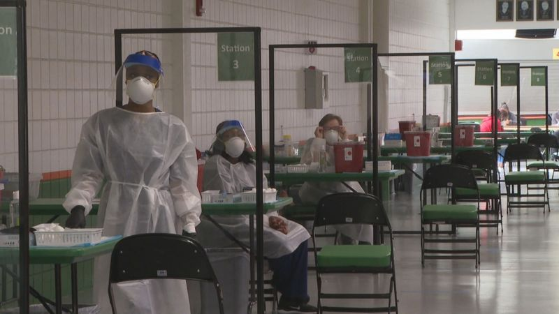 Workers help run a vaccination clinic on FAMU's campus.