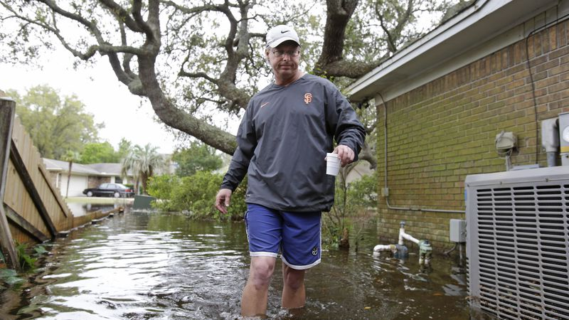 Homeowner Steve Owens walks to his backyard to check on the flooding of his residence Thursday,...
