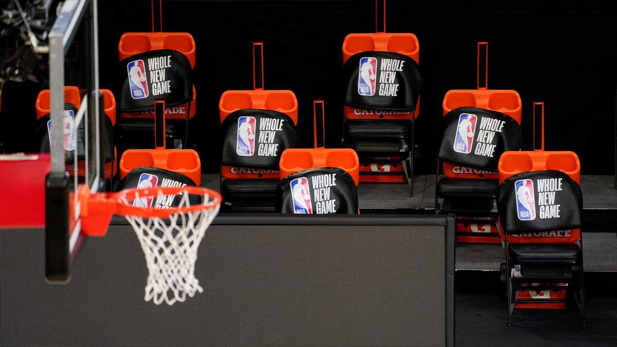 Seat covers are placed on socially distant chairs in the team bench area at a basketball arena...