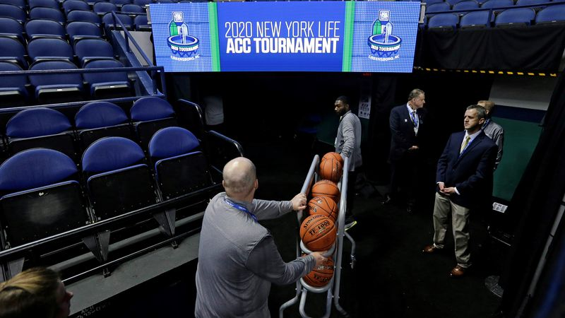 Personel remove the balls from the playing court after the NCAA college basketball games were...