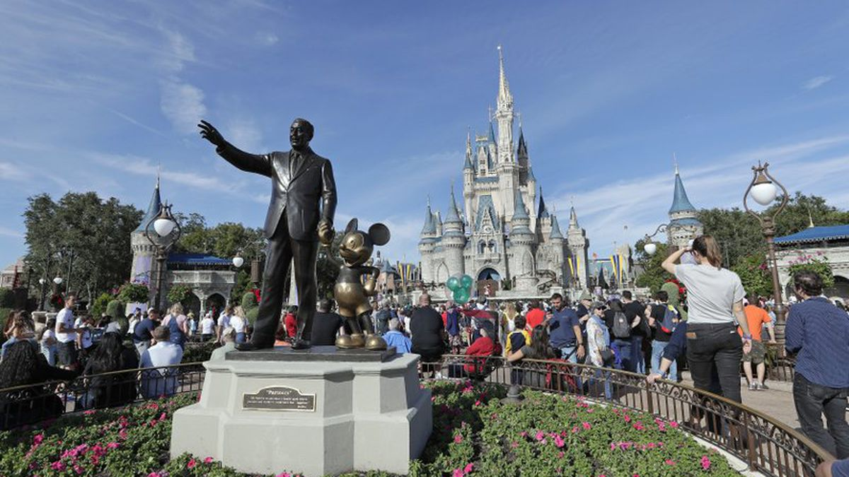n this Jan. 9, 2019, file photo, theme park guests walk near a statue of Walt Disney and Mickey...