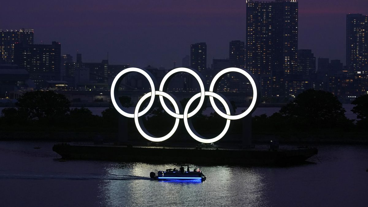 FILE - In this June 3, 2020, photo, the Olympic rings float in the water at sunset in the Odaiba section in Tokyo. The Japanese public is being prepared for the reality of next year's postponed Olympics where athletes are likely to face quarantines, spectators will be fewer, and the delay will cost taxpayers billions of dollars. In the last several weeks, IOC President Thomas Bach has given selected interviews outside Japan and hinted at empty stadiums, quarantines and virus testing.