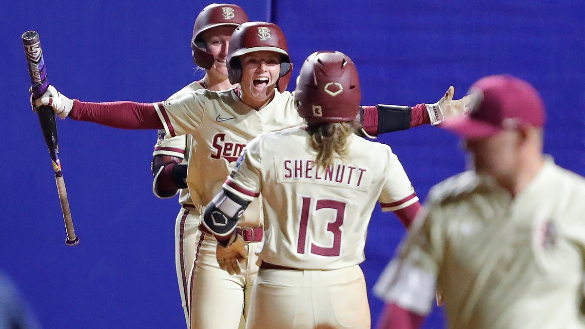 Florida State catcher Anna Shelnutt (13) is met by team mates at home plate after hitting a...