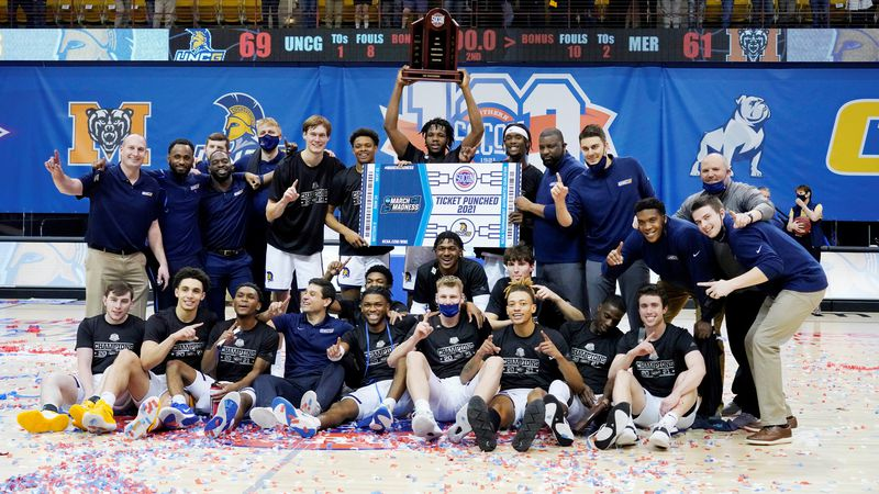 The UNC Greensboro men's basketball team holds the SoCon trophy and their ticket to the NCAA...