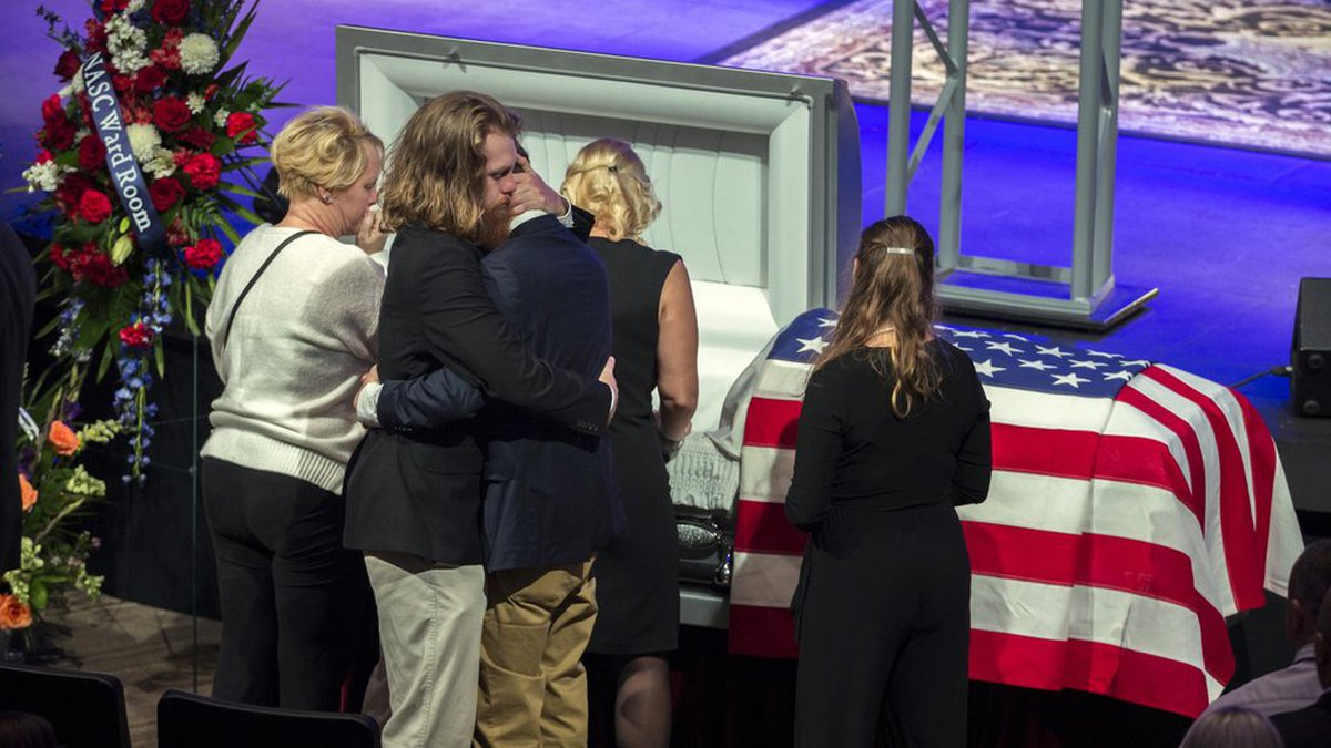 Dustin Walters, center left, hugs his brother Mason Walter, center right, during a funeral...