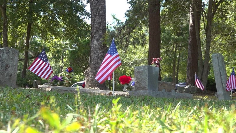 Monday, hundreds of red, white and blue flags placed on the headstones of black soldiers at...