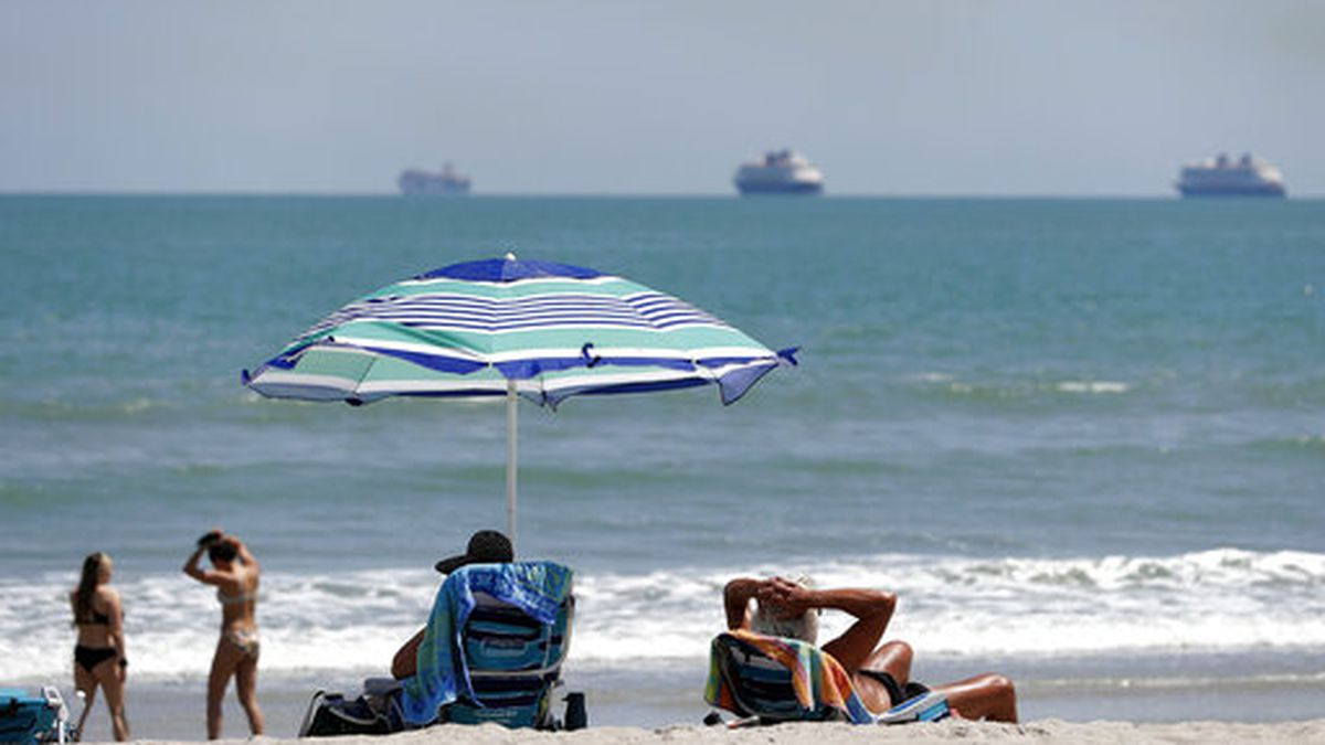 Despite a stay at home policy due to the coronavirus in Florida, beach goers enjoy the sun as cruise ships, without passengers, float offshore Saturday, April 4, 2020, in Cape Canaveral, Fla. Although some of the county beaches remained open, with out parking, many beach goers remained at home. (AP Photo/John Raoux)