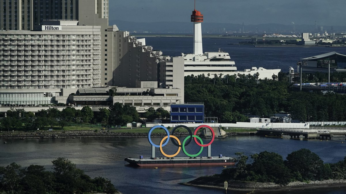 A barge with the Olympic rings mounted on it floats in the water ahead of the 2020 Summer...