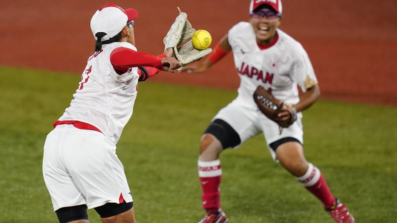 Japan's Yukiko Ueno, left, fields a ground out during a softball game against the United States...