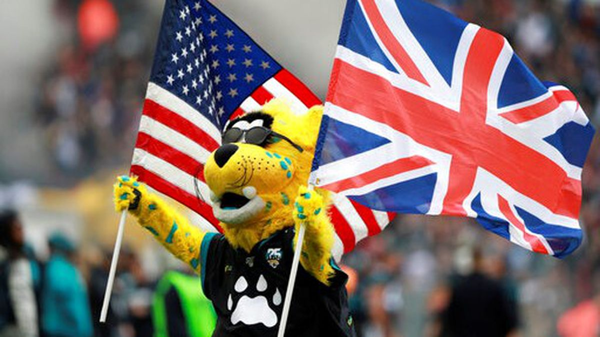 The Jacksonville Jaguars mascot carries the flags of the United States and Great Britian ahead...