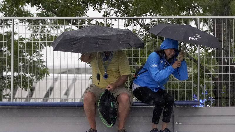FILE: Tennis fans take cover under umbrellas as rain begins to fall during the second round of...