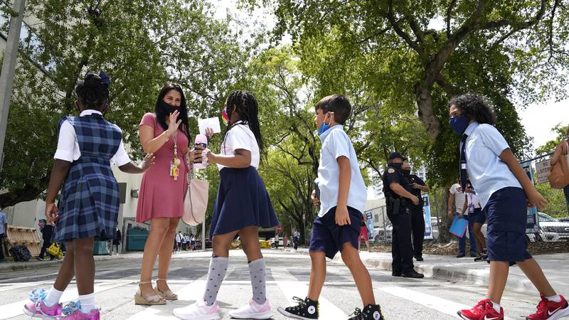 In this Monday, Aug. 23, 2021, file photo, teacher Vanessa Rosario greets students outside of...