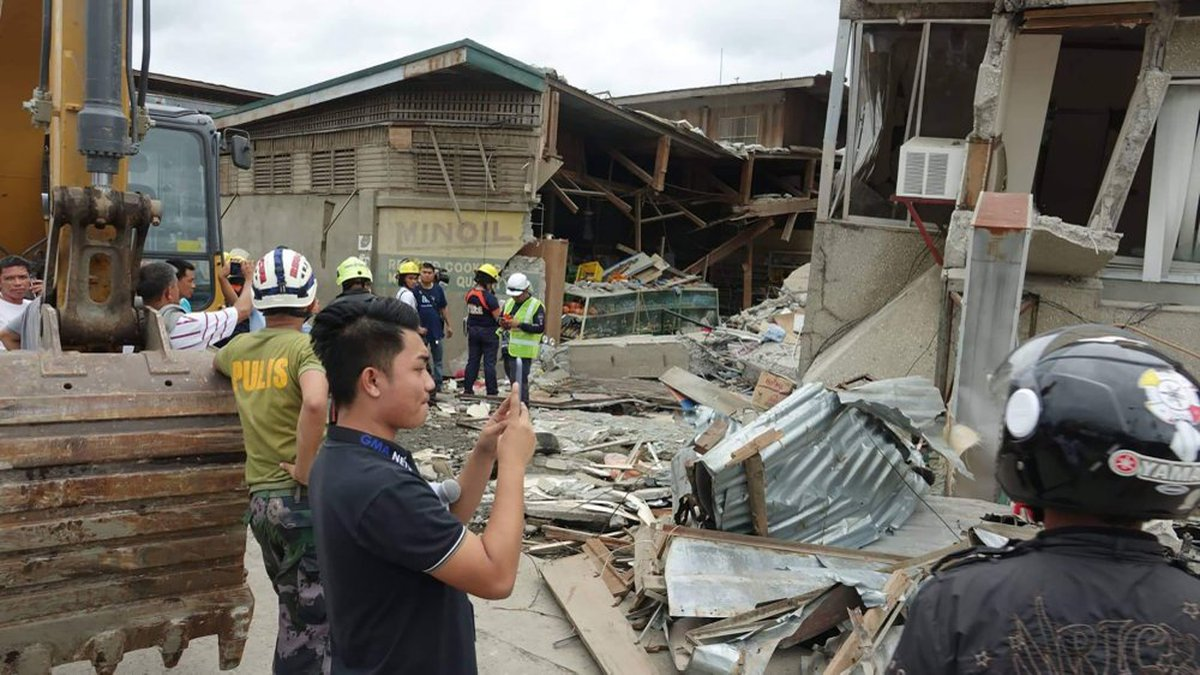 Residents and rescuers check damaged structures following an earthquake that struck Padada,...