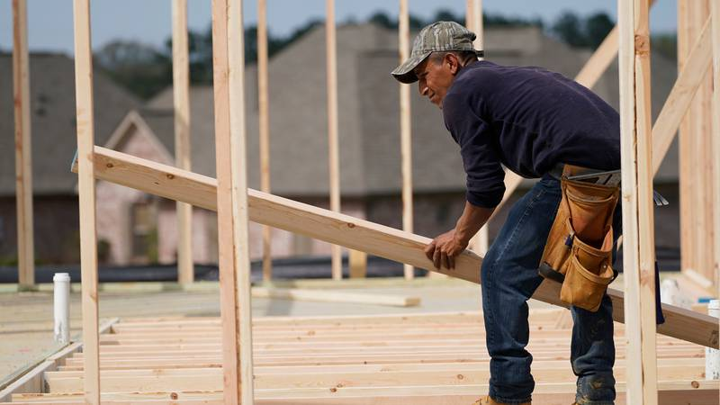 A carpenter aligns a beam for a wall frame at a new house site in Madison County, Miss.,...
