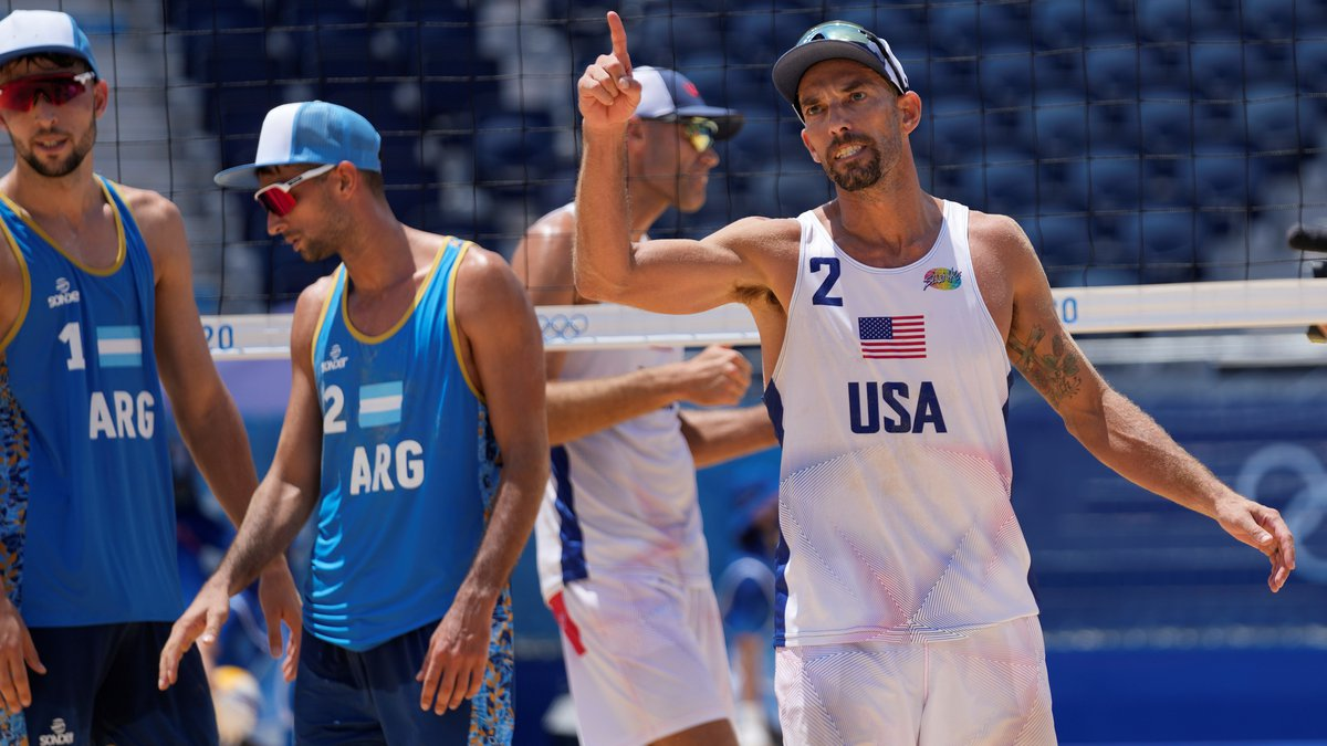 Nicholas Lucena, right, of the United States, celebrates winning a men's beach volleyball match...