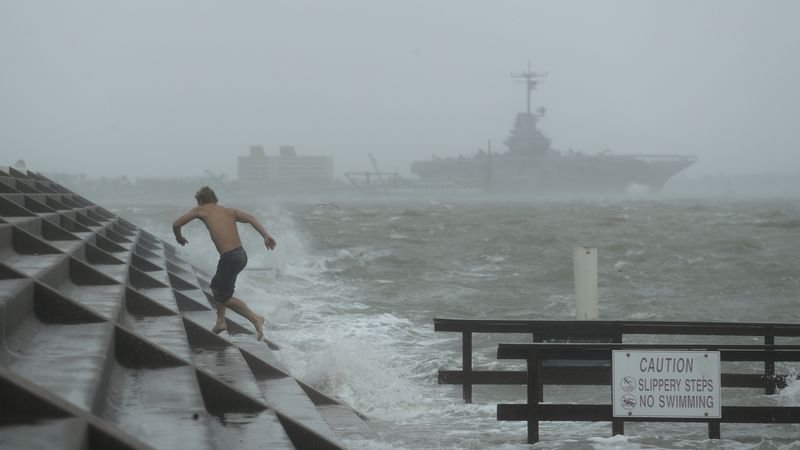 A man jumps from a wave as Hurricane Hanna begins to make landfall, Saturday, July 25, 2020, in...