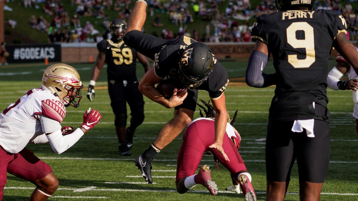 Wake Forest quarterback Sam Hartman, center top, dives into the end zone for a two-point...
