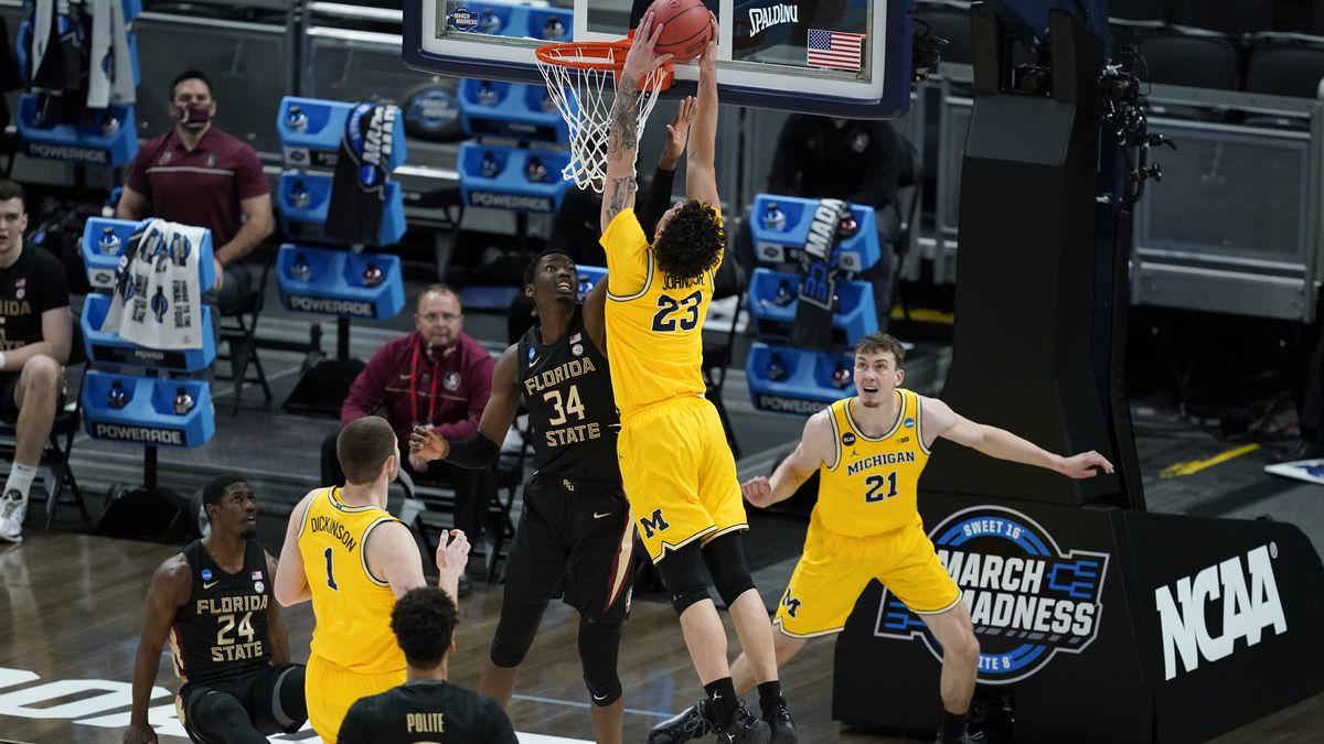 Michigan forward Brandon Johns Jr. (23) dunks over Florida State center Tanor Ngom (34) during...