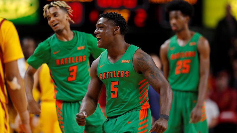 Florida A&M guard Nasir Core, center, celebrates the team's 70-68 win over Iowa State in an...