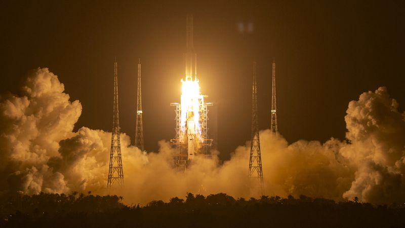 A Long March-5 rocket carrying the Chang'e 5 lunar mission lifts off at the Wenchang Space...