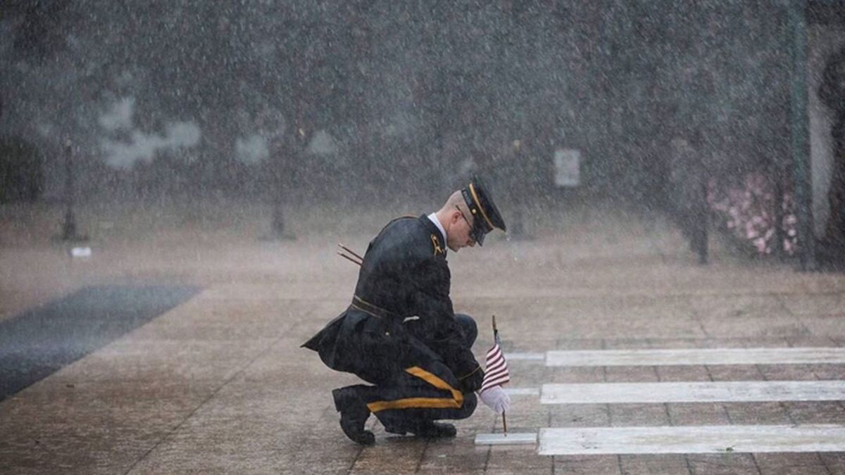A soldier with the 3rd U.S. Infantry Regiment placed flags at the Tomb of the Unknown Soldier on Wednesday during severe weather. (Source: 3d U.S. Infantry Regiment)