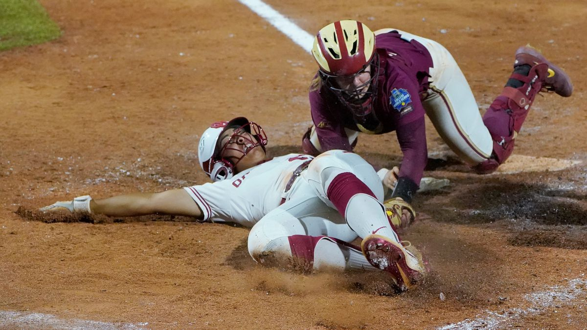Oklahoma's Tiare Jennings, left, is tagged out at the plate by Florida State catcher Anna...